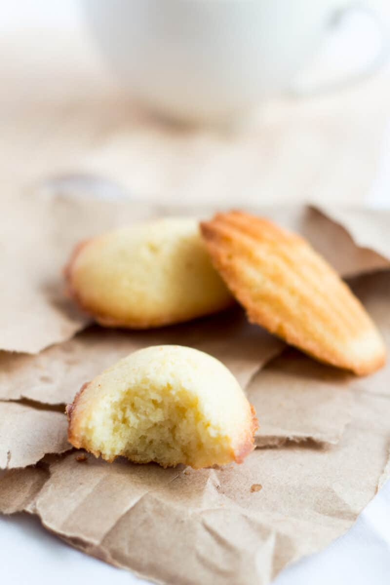 Madeleine Recipe: 2 madeleines and another half eaten on brown paper
