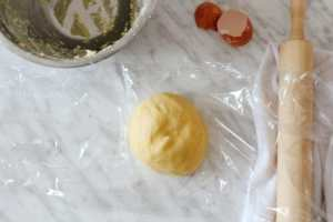 dough ball on a marble table with a cracked egg