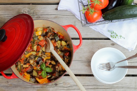 Menu planning: Big red one pot full of easy French ratatouille with a white bowl on a wood background