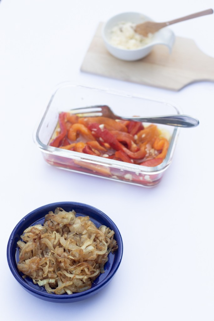 Caramelized onions in a blue dish, garlicky peppers in a glass dish and compound butter with a wooden knife