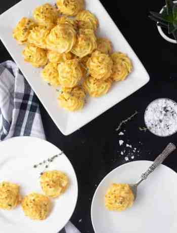 Duchess potatoes piled in a rectangle dish and small round plates with some served, rustic serving spoon. Black background.