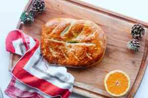 Sweet bread on a wooden tray, napkin and half an orange on the side.