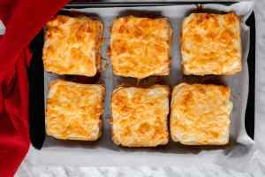 Top view of baked croque-monsieur sandwiches on a baking sheet.