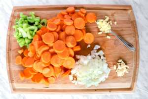 Mise en place of cut veggies on a wooden cutting board