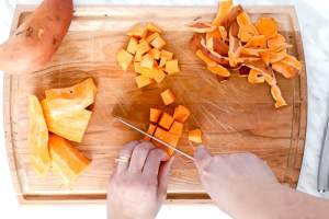 Wood cutting board and 1 whole sweet potato and a hand cutting into cubes another one