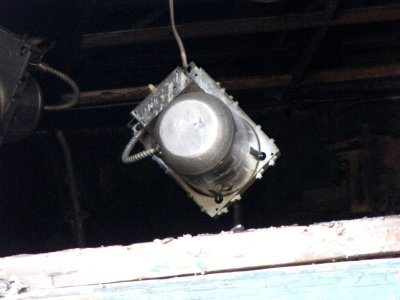 Light fixture hanging by a wiring conduit, viewed through the middle window on the second floor, on the back side.