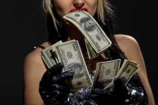 photo of woman holding money in teeth