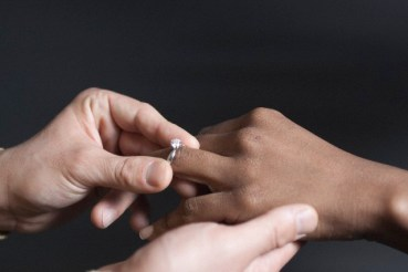 New York City, New York State, USA --- Man putting a wedding ring on a woman's finger --- Image by © Ocean/Corbis