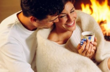 Couple snuggled up together in front of the fire