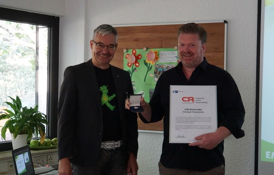 Christoph Timmerarens (rechts) als frisch gebackener CSR-Botschafter begrüßt Michael Pieck (links) als Vertreter des CSR Kompetenzcenter (@EMIKO Gruppe).