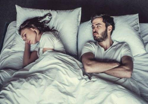 man looking woman in bed