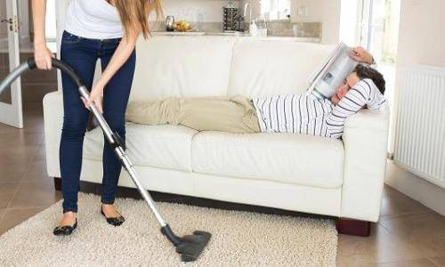 woman cleaning and man resting