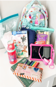 Back pack, snack bags, blanket, book, clothes, water bottle, sketchbook and pencils, tablet to show what to put in kids' carry-ons for flights.