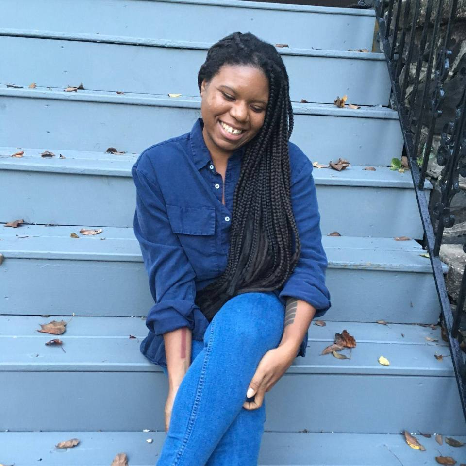 Author Jordannah Elizabeth sitting on stairs and smiling