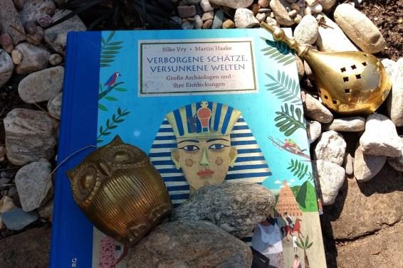 Buch auf dem ein Pharao abgebildet ist, darauf Steine, daneben ein glänzendes Artefakt
