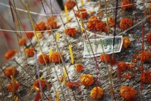 "A banknote is left among flowers and candles on a sand stupa during ""Pi Mai Lao,"" or Lao New Year celebrations in Vientiane"