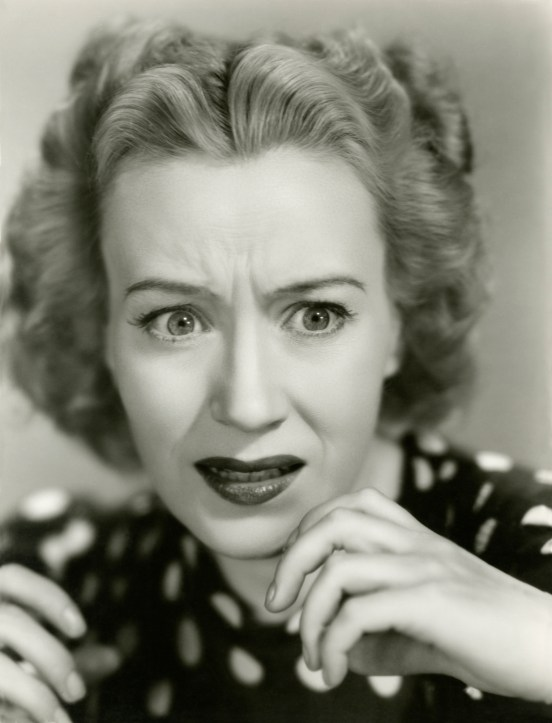 Vintage black and white photo of a woman looking extremely anxious.