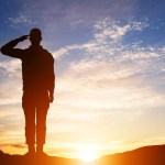 Picture of a soldier saluting at sunset.