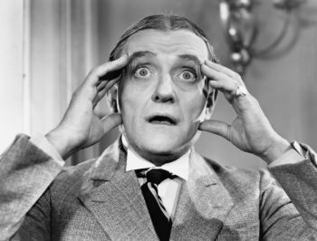 Vintage black and white photo of a man holding his head like he can't believe what he's seeing and hearing.