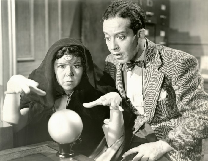 Vintage photo of a man in a suit consulting with a fortune teller who's looking into a crystal ball.