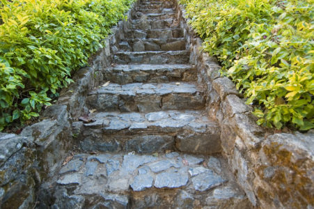 Outdoor stone walkway with stairs leaving up to something out of view.