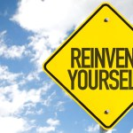 "Blue cloudy sky behind a yellow road sign that says ""reinvent yourself."""