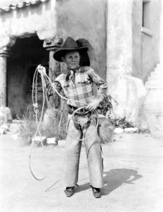 Young boy dressed as cowboy ready to lasso someone