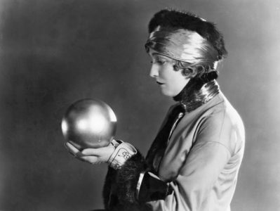 Vintage photo of woman holding crystal ball asking if she spends as much as other Boomers.
