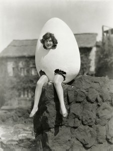 Vintage black and white photo of woman sitting inside her giant nest-egg, with only her head and legs exposed.