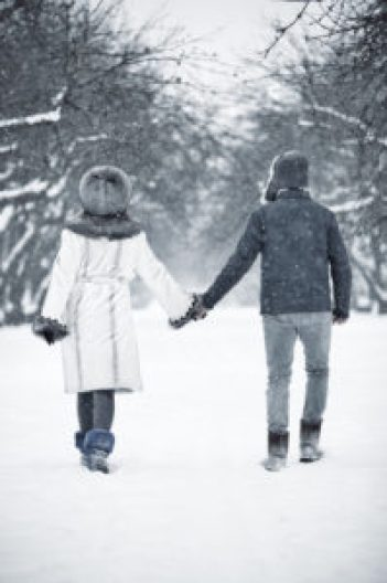 Boomer couple holding hands walking through snow at a continuing care retirement community.