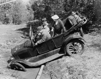 Vintage b/w photo of trio in a convertible Model A car with one lamenting they should have reviewed concept of stock risk.
