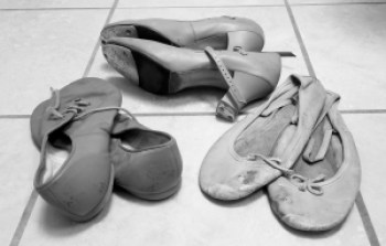 Black and white photo of three pairs of dance shoes; tap, ballet, jazz.