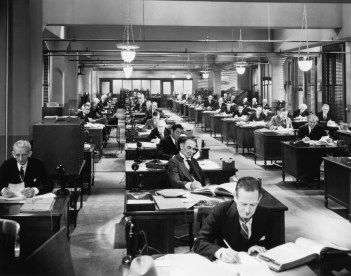 Black and white vintage photo of hundreds of actuaries and MBAs working at their desk building annuities.