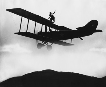 Black & white vintage photo of daredevil on wing of a biplane, announcing she wants to buy an annuity.