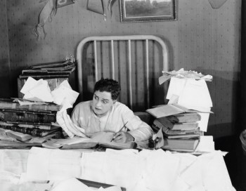 B&W photo of wild-eyed man drowning in annuity paper work, realizing he needs to lose his bad annuity