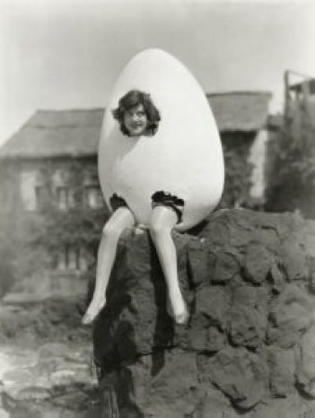 Retro black and white photo of woman in sitting inside a giant egg with only her head and dangling legs exposed.