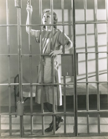 Retro black and white photo of woman in jail cell complaining jail staff are as inflexible as her immediate and longevity annuities.