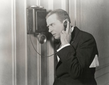 Black and white retro photo of man in suit talking on a wall phone