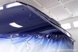 Erste Lackschicht in dunkelblau auf der Comfortina 38 Segelyacht. Heckansicht in der Lackierkabine der Bootswerft Baumgart in Dortmund