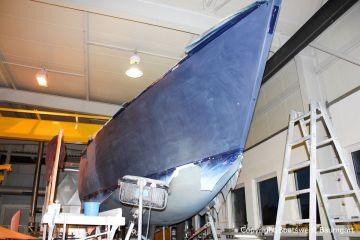 Die erste Lackschicht wird angeschliffen. Die Comfortina 38 in der Bootswerft. Steuerbordseite in der Werfthalle der Bootswerft Baumgart in Dortmund