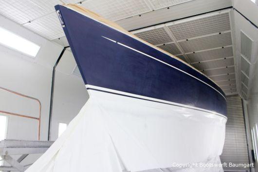 Fertig lackierter Zierstreifen und Wasserpass. Backbordseite in der Lackierkabine der Bootswerft Baumgart in Dortmund