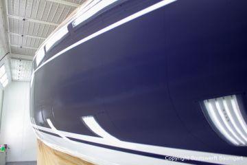 Backbord Seitenansicht der fertig lackierten Comfortina 38 in der grossen Lackierkabine der Bootswerft Baumgart in Dortmund