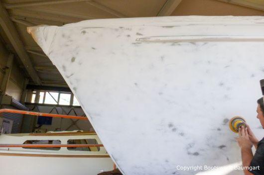 Schleifarbeiten am Rumpf einer Vilm 106 in der Werfthalle der Bootswerft Baumgart in Dortmund