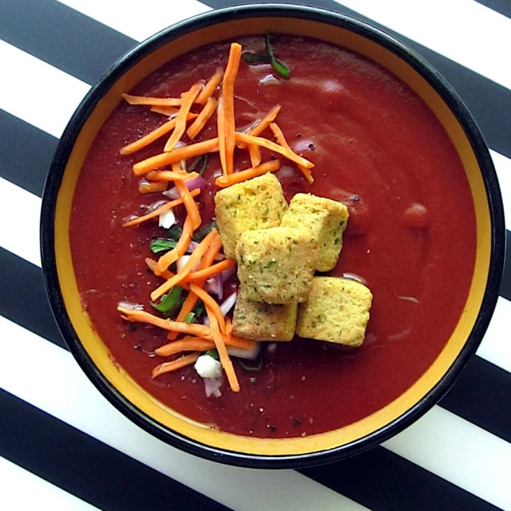 Roasted Red Pepper and Cherry Gazpacho Garnished with carrots, green onion, red onion, and croutons.