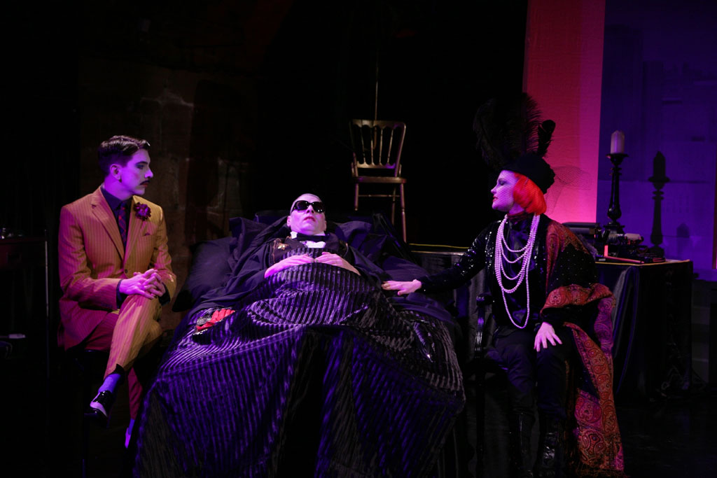 A man in a black suit lies in a bed. Gathered around him are a man in a brown suit with a small moustache and a woman with short red hair dressed in a fancy black dress and a long pearl necklace.