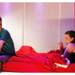 The stage is set like a bedroom with red walls and red bedsheets. A woman sits up in bed looking at a man who is sat on the foot of the bed. He looks back at her.