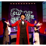 A man in a long red coat and a black top hat stands at the front of the stage with his arms out. There are actors in the background wearing what looks like Victorian style clothing.