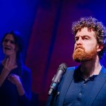 An actor with a ginger beard and curly hair stands in front of a microphone looking stern. We see a woman in the background signing.