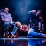 A man lies on the floor of the stage in front of an empty wheelchair. We see a man in a wheelchair behind him.