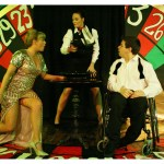 A large painted roulette wheel makes the background of the stage. Two actors sit across a small roulette table and watch the little ball that has just been thrown.